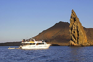 Dive boat by Pinnacle Rock, the eroded remains of a tuff cone, by the the volcano on Isla Bartolome. Galapagos, January 2005. - Bryan and Cherry Alexander