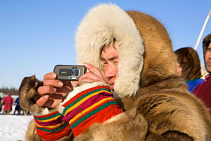 Nenets spectator using his mobile phone to photograph a reindeer race at a herders festival in the Yamal. Western Siberia, Russia, February 2009. Editorial use only.  -  Bryan and Cherry Alexander