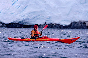 Eco tourist in a sea kayak paddling past a glacier near Port Lockroy. Antarctic Peninsula Editorial use only.  -  Bryan and Cherry Alexander