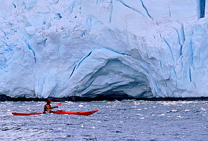 Eco tourist in a sea kayak paddling past a glacier near Port Lockroy, Antarctic Peninsula.  -  Bryan and Cherry Alexander