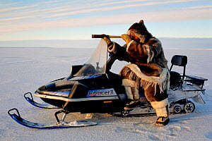 Inuk in fur clothing steadying his telescope on snowmobile while out hunting. Igloolik, Nunavut, Canada, 1995. - Bryan and Cherry Alexander