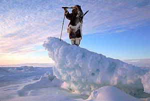 Inuk in fur clothing on ice ridge, looking for seals with telescope. Igloolik, Nunavut, Canadian Arctic, 1995. - Bryan and Cherry Alexander