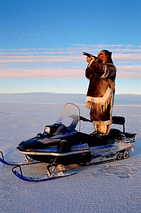 Inuit hunter standing on his snowmobile to scan the surrounding ice for seals. Igloolik, Nunavut, Canada, 1995. - Bryan and Cherry Alexander