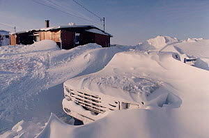 Truck covered in snow by winter snow storms in Igloolik, Nunavut, Canada, 1990. - Bryan and Cherry Alexander