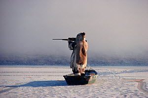 Inuk standing in floe edge boat at the ice edge, aiming his rifle while hunting. Igloolik, Nunavut, Canada, 1990 - Bryan and Cherry Alexander