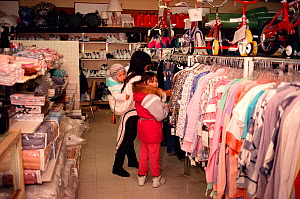 Inuit mother and girls shopping for clothes in a shop at Igloolik, Nunavut, Canada, 1990. - Bryan and Cherry Alexander