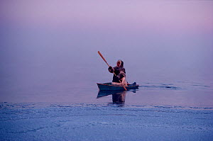 Inuit hunter paddling a floe edge boat through frost smoke while seal hunting at the ice edge near Igloolik, Nunavut, Canada, 1990. - Bryan and Cherry Alexander