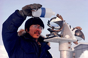 Inuit technician cleaning a sunlight recorder at Igloolik Research Centre. Nunavut, Canada, 1990. Editorial use only. - Bryan and Cherry Alexander