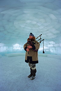 John MacDonald, a Scot who lives in Canada's arctic, playing the bagpipes in a large igloo. Nunavut, Canada, 1999. - Bryan and Cherry Alexander