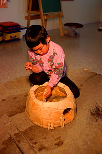 Inuit girl playing with model igloo in the Headstart early learning program. Igloolik, Nunavut, Canada, 1999. - Bryan and Cherry Alexander