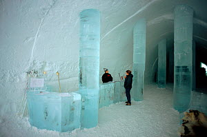 Reception area in Ice Hotel with ice desk and warmly dressed receptionist. Jukkasjarvi, Sweden, 2003.  -  Bryan and Cherry Alexander