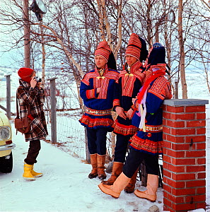 Tourist photographing group of Sami men in traditional costume. Kautokeino, Norway, 1972.  -  Bryan and Cherry Alexander