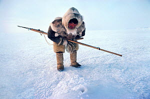 Fur clad Inuk waiting to harpoon seal at breathing hole. Northwest Greenland, 1980.  -  Bryan and Cherry Alexander