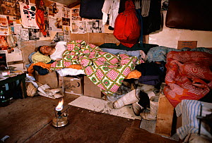 Inuk asleep in hut with stove for warmth. Northwest Greenland, 1980.  -  Bryan and Cherry Alexander
