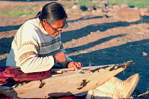Inuit woman sewing wet seal skins onto wooden kayak frame. Qeqertat, Thule, Northwest Greenland, 1977.  -  Bryan and Cherry Alexander