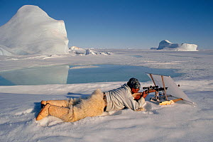 Inuit hunter shooting seal from behind concealing white linen screen. Northwest Greenland, 1997 - Bryan and Cherry Alexander