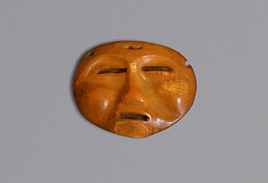 Miniature ritual mask carved from Walrus ivory (circa 1000 BC - 1000 AD) Bering Strait, Chukotka, Siberia, Russia.  -  Bryan and Cherry Alexander