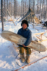 Evenk herder at winter camp in the forest, holding a pair of traditional Evenk Reindeer / Caribou skin covered skis. Surinda, Evenkiya, Central Siberia, Russia, 1997.  -  Bryan and Cherry Alexander