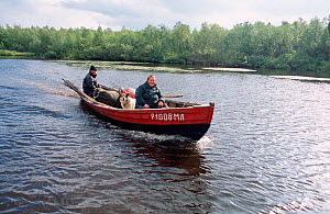 Sami Woman and son returning to Lovozero by boat after summer fishing trip. Kola Peninsula, Northwest Russia, 2005. - Bryan and Cherry Alexander
