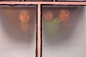 Girls looking through a window from inside their home in Verkhoyansk, Yakutia ,Siberia, Russia, 1999. - Bryan and Cherry Alexander