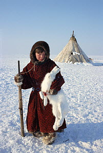 Tundra Nenets boy posing with Arctic hare (Lepus arcticus) he has shot. Gydan Peninsula, Western Siberia, Russia, 2000. - Bryan and Cherry Alexander
