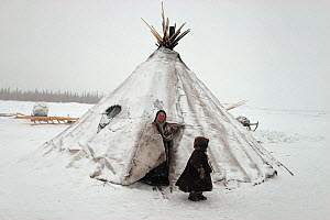 Nenets woman and boy at entrance to snow covered tent. Yamal, Siberia, Russia, 1993 - Bryan and Cherry Alexander
