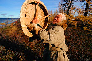 Elderly Nenets man holding sacred drum, which he made in 1946. Yamal, Western Siberia, Russia, 2001. - Bryan and Cherry Alexander