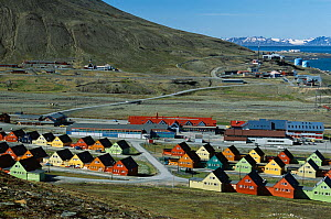 Brightly coloured wooden homes by the shopping centre, with view to Gamle Longyearbyen. Svalbard, Norway, 2004.  -  Bryan and Cherry Alexander