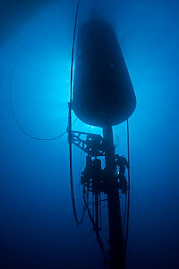 Diver working on a large wave-energy buoy off Kaneoho Bay, Oahu. The 40-kW experimental buoy employs the bobbing motion of the buoy to drive an electrical generator, that sends power to the island via... - David Fleetham