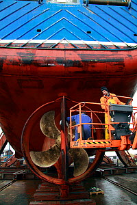 Engineers carrying out hull repairs on a fishing vessel in dry dock, Skagen, Denmark. March 2010. - Philip Stephen