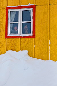 Two ladies looking through their window. (Mayor Asi Chemnitz and her secretary Anna of Nuuk Commune) This is the second largest Commune of the world.  Ittoqqortoormiit. Scoresbysund, North East Greenl...  -  Uri Golman