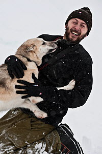 Portrait of photographer Uri Golman with Greenland husky sled dog, North East Greenland. March 2009. Model released - Uri Golman