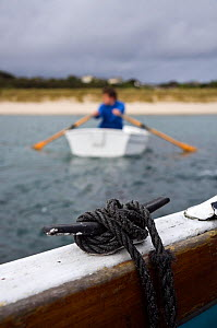 Man rowing a tender towards the beach from a boat off St. Martin's, Isles of Scilly, UK. Model Released  -  Merryn Thomas