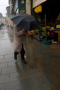 Man using umbrella as shield against rain in storm. Example of impact of climate change on ordinary people. Denbigh, North Wales, UK. July 2009.  -  David Woodfall