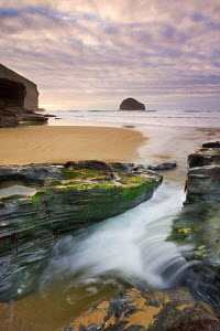 Freshwater stream flows through a channel towards the beach at Trebarwith Strand, Cornwall, England. February 2009 - Adam Burton