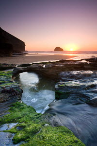 Water channel flowing beneath natural rock arch at Trebarwith Strand beach in Cornwall, England. Spring - April 2009  -  Adam Burton