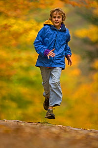 Boy, aged 12, running in autumn woodland, upstate New York,  USA, model released - John Cancalosi