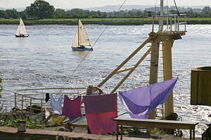 Woman pauses  from hanging washing, to watch the bore and pleasure craft. Severn Estuary. England, August 2009  -  David Woodfall