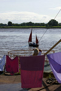 Woman hanging her washing, pauses to watch the bore and pleasure craft. Severn Estuary. England, August 2009  -  David Woodfall