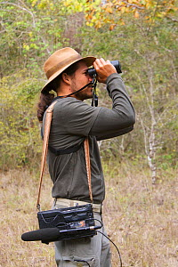 Local guide with recording equipment, looking through binoculars, birdwatching in the Pantanal, Brazil. Model Released.  -  Piper Mackay