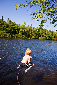 Boy playing on rope swing over the Androscoggin River, Mollidgewock State Park in Errol, New Hampshire, USA, August 2008. Model released.  -  Jerry Monkman