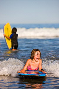 Young girl boogie boarding at Hampton Beach, New Hampshire, USA, August 2008. Model released.  -  Jerry Monkman