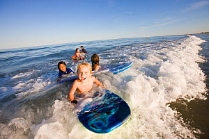 Children on boogie boards in surf at Hampton Beach, New Hampshire, USA, August 2008. Model released.  -  Jerry Monkman