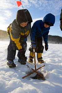 Two young brothers ice fishing on the West River in Brattleboro, Vermont, USA, February 2007. Model released.  -  Jerry Monkman