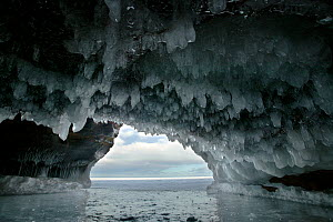 Ice hanging from arch in sea cave carved in soft sandstone cliffs, frozen lake, Squaw Bay, Lake Superior, Apostle Islands National Lakeshore, Wisconsin, USA, February 2009  -  Thomas Lazar