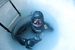 Camerman Doug Allan at frozen water surface of drilled ice hole, BBC film crew, McMurdo Sound, Ross Sea, Antarctica, November 2008  -  Neil Lucas