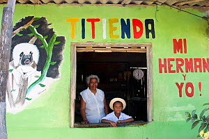 """""""Titienda"""" shop - owner with grandson tending their small grocery store in Los Limites, Colombia. Advertising the presence of the cotton-top tamarin in their forests helps educate the community and is...  -  Lisa Hoffner"""
