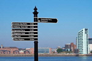 Signpost on Seacombe promenade showing distance and direction to points of interest. Merseyside, England. May 2010. - Norma Brazendale