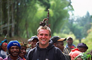 Cameraman Tom Clarke, with a juvenile domestic chicken (Gallus gallus domesticus) on his head, Tari Valley, Papua New Guinea, during filming for the BBC series Planet Earth, August 2004.  -  Tom Clarke