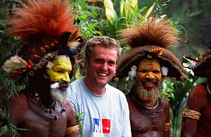 Cameraman Tom Clarke, with Huli wigmen dressed in traditional clothing, Tari Valley, Papua New Guinea, during filming for the BBC Planet Earth series, August 2004.  -  Tom Clarke